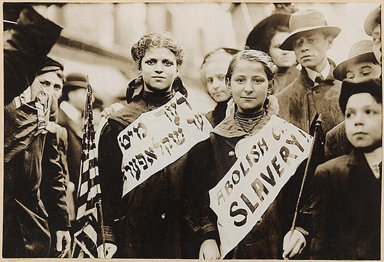 "Children wearing sashes in Hebrew and English bearing the words ""Abolish Child Slavery"""