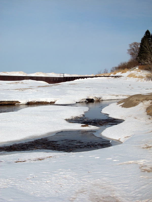 A creek running through a winter-locked shore.
