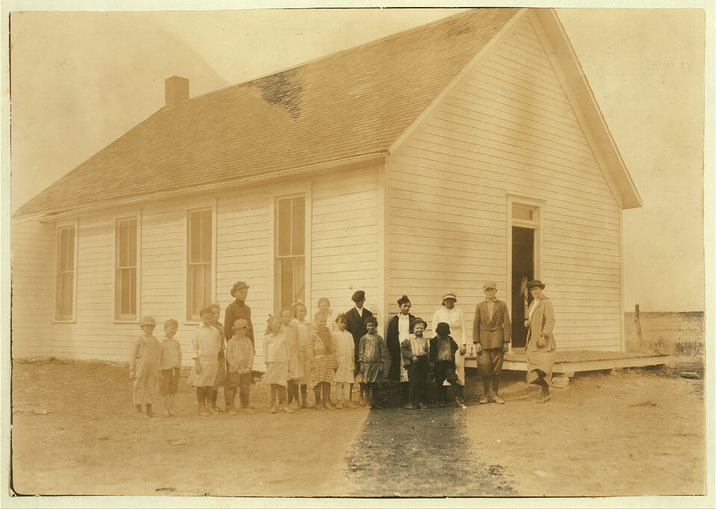 Teacher and students stand outside a one-room schoolhouse.