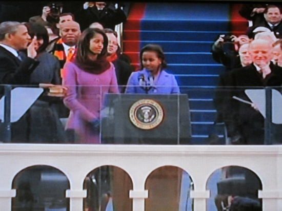 President Obama taking the oath of office as his family looks on (Photograph of PBS coverage)
