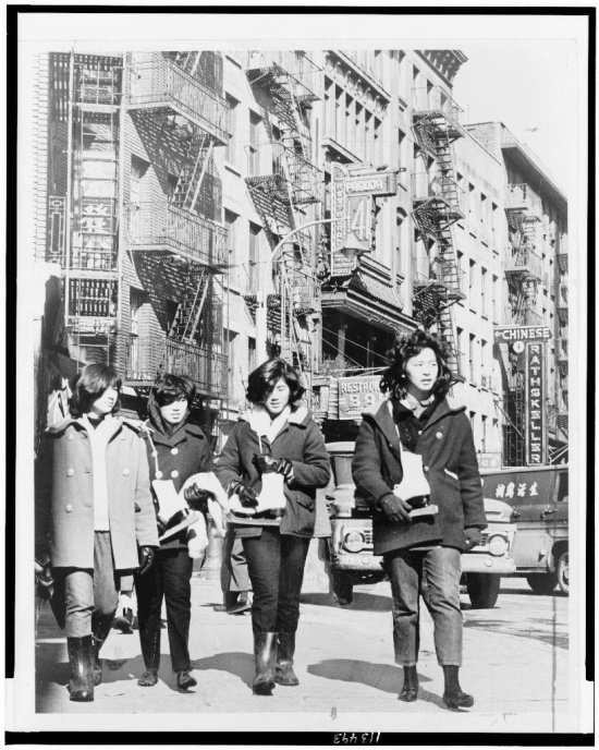 Four young women with ice skates on a Chinatown street.