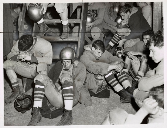 High-school football players slump in attitudes of introspection and gloom.