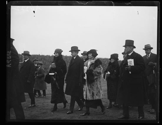Black-and-white photograph of well-dressed men and women traipsing across an open field.