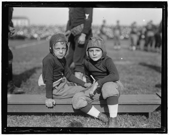 Two boys on the sidelines in football helmets (Courtesy of the Library of Congress)