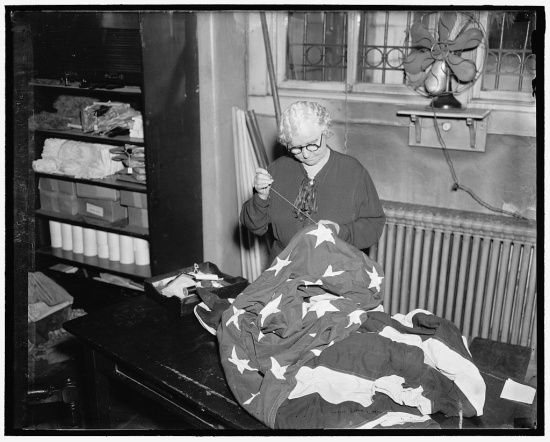 A woman mends the American flag in a back room of the Capitol