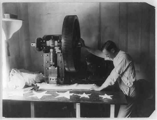 Man cutting out stars in a flag factory (Courtesy Library of Congress)