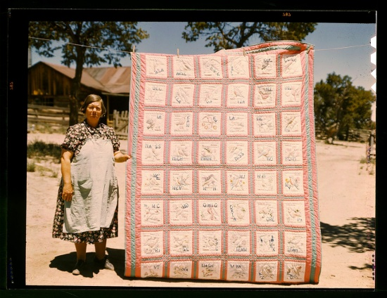 A farmwoman in house dress outside, with quilt she made hanging next to her from a clothesline.