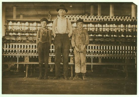 An overseer and two small grimy boys face the camera in a textile mill.