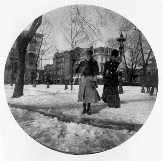A girl holding a Kodak camera and standing in a snowy Washington DC smiles for an unknown photographer.