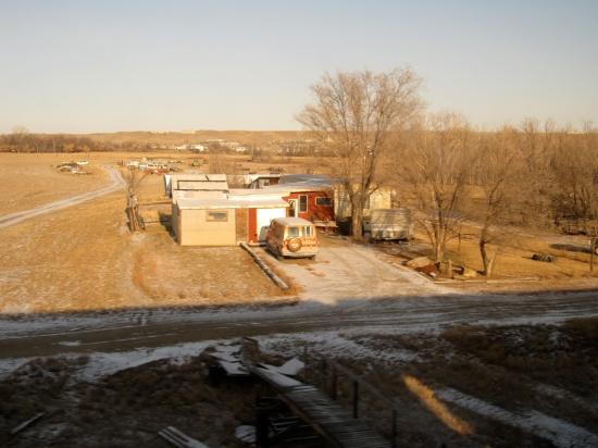 Western home in junk-strewn landscape.
